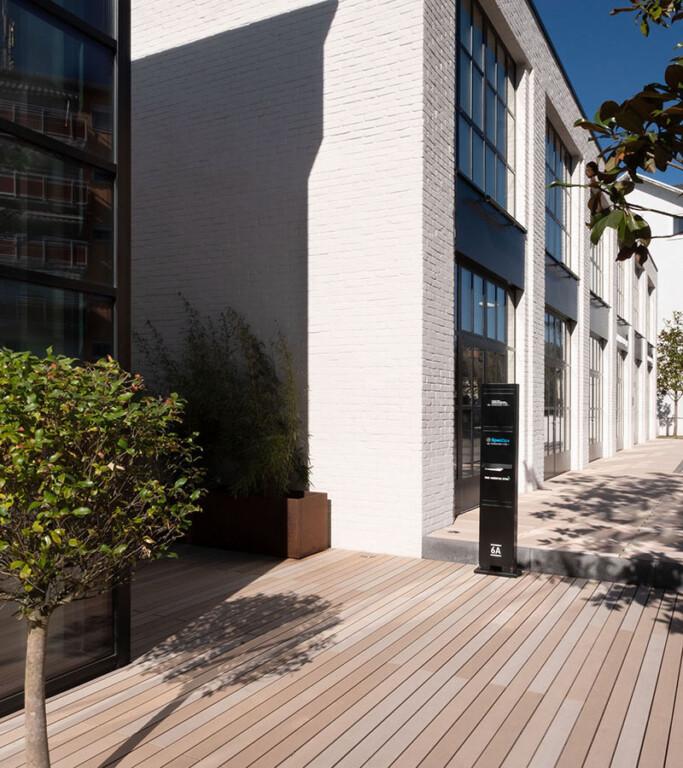 Helle WPC Terrassendielen von MYDECK auf einer Terrasse vor einem Backsteingebäude.