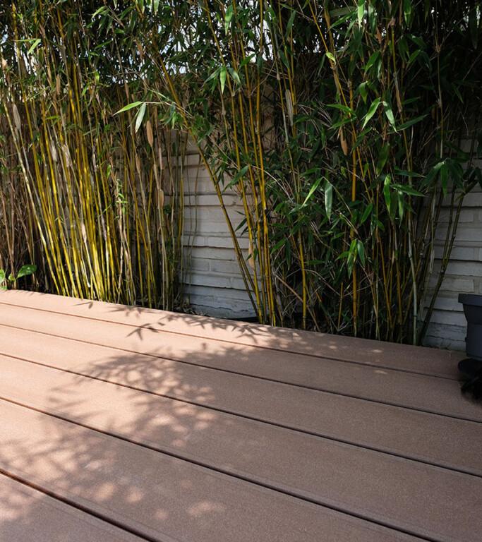 Dunkelbraune WPC Terrassendielen auf Terrasse vor Bambus