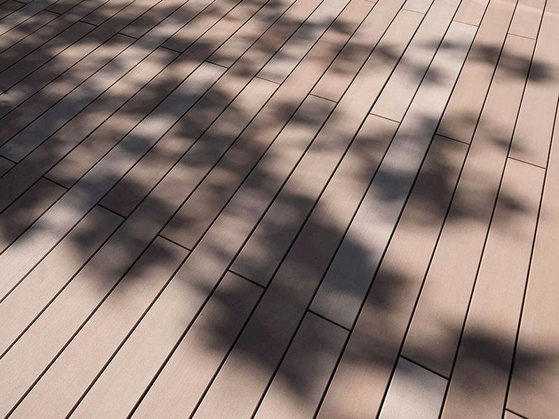 Verlegemuster glatte helle WPC Terrassendielen auf Terrasse mit Schafften von Bepflanzung
