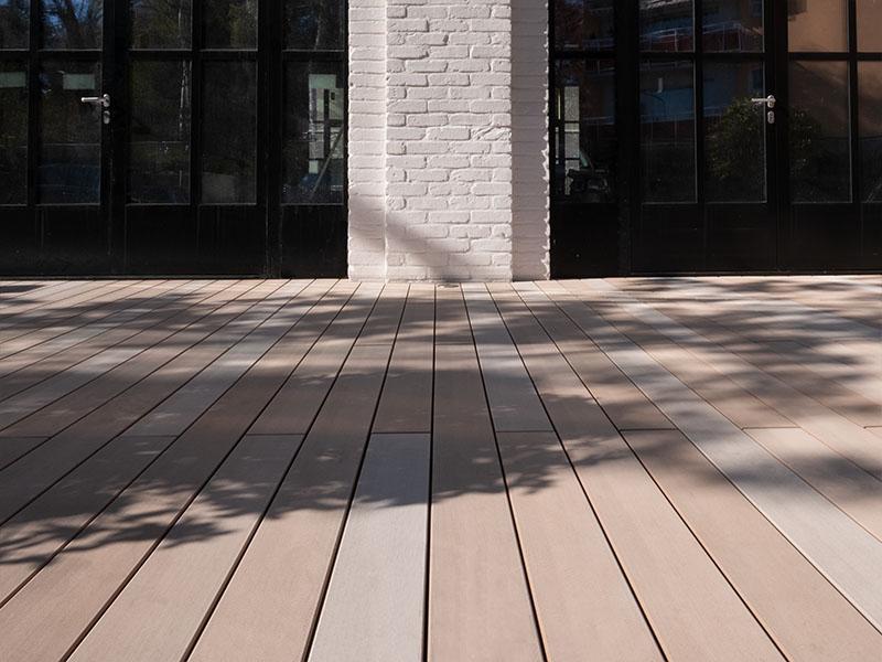 Terrasse mit hellen WPC Terrassendielen in Sandtönen von hellbraun, bis hellgrau vor Backsteingebäude