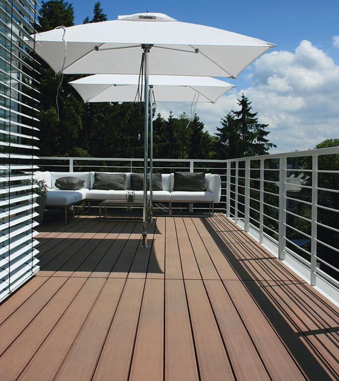 Balkon mit braunen WPC Massivdielen auf modernem Balkon mit weißen Outdoormöbeln