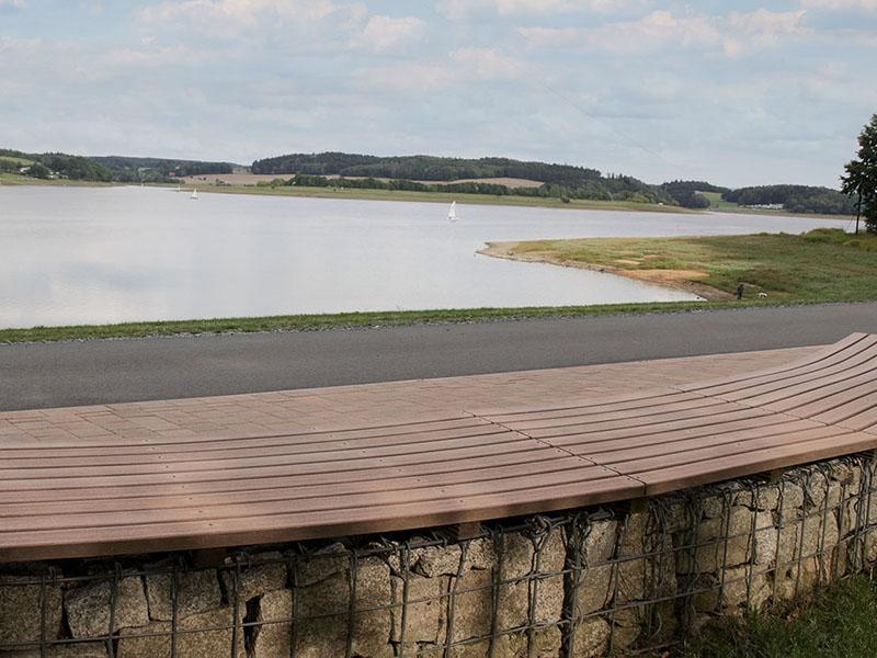 Bank mit Sitzfläche aus braunen WPC Dielen und Blick auf See