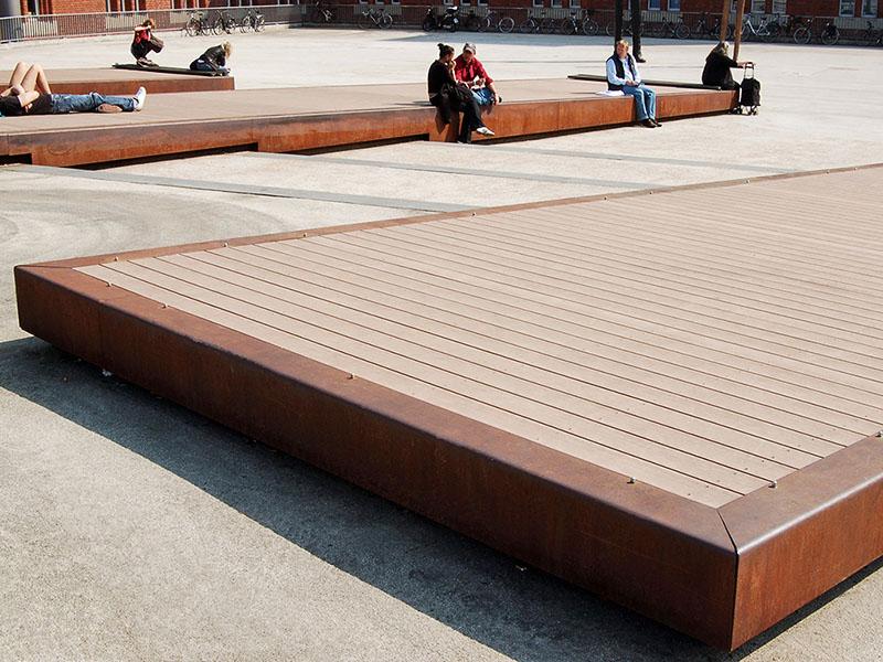 Hellbraune WPC Dielen (massiv) auf Liegefläche auf öffentlichem Platz, Blende aus Cortenstahl