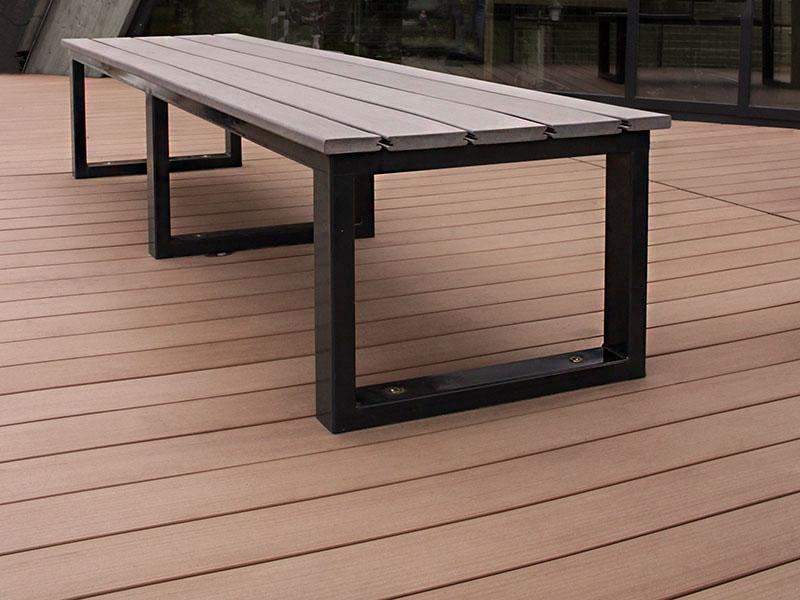 Bank mit grauen WPC Dielen als Sitzfläche auf Terrasse mit WPC Außendielen