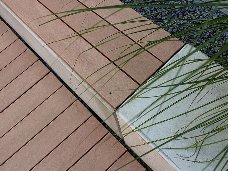 WPC Terrassendielen dienen als Sitzfläche für die Bank und unterbrechen so das Betonmäuerchen